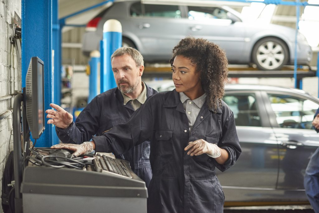 A female mechanic is working on computer diagnostics on  a car in a garage repair shop. She is wearing blue overalls.  She is typing into the computer and being advised by her colleague , boss , or instructor.